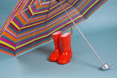 Red children rain boots and a colorful umbrella — Stock Photo