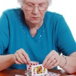 Elderly woman making house with cards — Stock Photo