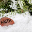 Faith stone in snow - Stock Photo