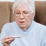 Senior woman reading a thermometer — Stock Photo