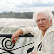 Senior woman sitting at edge of niagara — Stock Photo