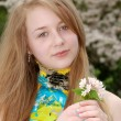 Young female teenager holding flowers — Stock Photo