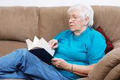 Senior woman turning pages of a book — Stock Photo