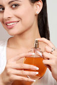 Young woman holding perfume bottle — Stock Photo