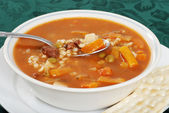 Closeup beef barley soup with a spoonful — Stock Photo