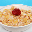 Foto Stock: Closeup of bowl of flaky cereal with strawberry
