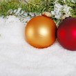 Gold and red christmas ball in the snow — Stock Photo