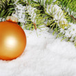 Gold christmas ball in snow - Stock Photo