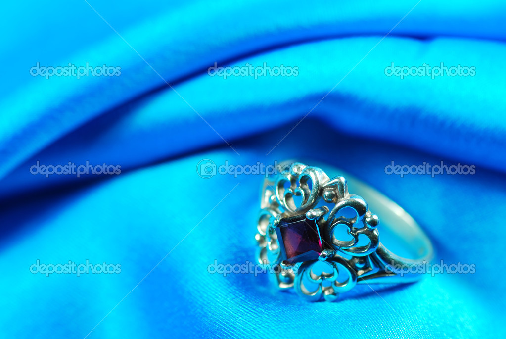 Closeup of a Garnet ring on blue fabric  — Stock Photo #3444500