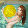 Woman in a blue bikini playing with a yellow beachball — Stock Photo