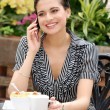 Woman talking on cell phone in outdoor cafe — Stock Photo