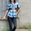 Young woman leaning on barn — Stock Photo