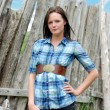 Young woman standing near old wood post fence — Stock Photo