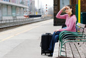 Woman sitting on bench looking for the train — Stock Photo