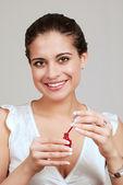 Young woman using nail polish — Stock Photo