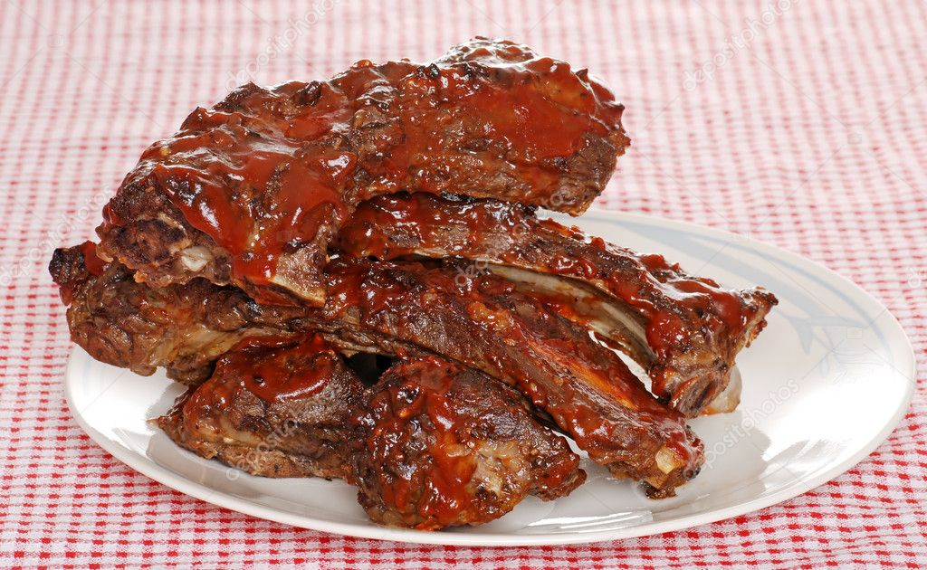 Stack of barbecue beef spare ribs with sauce on a red and white checkered tablecloth  — Stock Photo #3450081