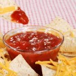 Macro dipping nachos and cheese in salsa — Stock Photo