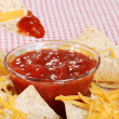 Stock Photo: Macro dipping nachos and cheese in salsa