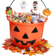 Child halloween pumpkin bucket with candy and fall leaves — Stock Photo