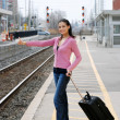 Woman hitchhiking at railroad station — Stock Photo