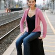 Stock Photo: Woman sitting on luggage waiting for train