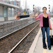 Woman with luggage waving at train station — Stock Photo