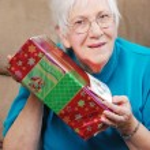 Happy senior woman shaking her christmas present — Stock Photo