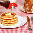 Maple Syrup being poured on a stack of pancakes — Stockfoto