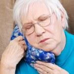 Senior woman using medical herb hot pack — Stock Photo