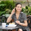 Young woman talking on a cell phone over lunch - Stock Photo