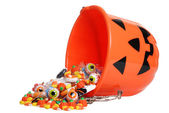 Child halloween pumpkin bucket spilling candy — Stock Photo