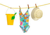 Girls beach wear and toys on clothes line — Stock Photo