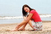 Young happy woman sitting on beach — Stock Photo