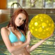 Sexy brunette holding a yellow polka dot beach ball — Stock Photo