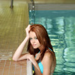 Sexy brunette woman leaning on swimming pool edge — Stock Photo #3813626