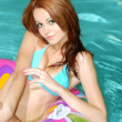 Stock Photo: Sexy brunette womfloating on pool toy