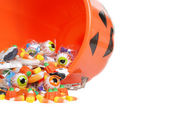 Macro spilled halloween candy and pumpkin bucket — Stock Photo
