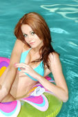 Sexy brunette woman floating on pool toy — Stock Photo