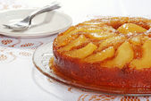 Upside down pear cake with plates and forks — Stock Photo