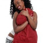 Playful jamaican woman hugging a pillow — Stock Photo #3859098