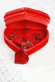 Red necklace in heart jewelry box — Stock Photo