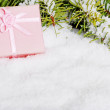 Pink christmas present in snow — Stock Photo