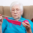 Senior putting away her knitting — Stock Photo