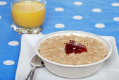 Oatmeal with strawberry jam and orange juice — Stock Photo