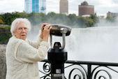 Senior surprised at niagara falls binoculars — Stock Photo