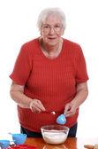 Senior vrouw meten terwijl het bakken — Stockfoto