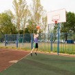 Stock Photo: Young men playing street basketball at court playground