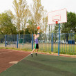 Young men playing street basketball at court playground - Stock Photo