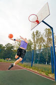 Young men playing street basketball at court playground — Stock Photo