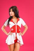 Sensual brunette nurse posing on color background — Stock Photo